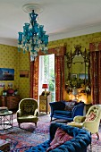 Traditional, English interior with strong colour contrasts between yellow patterned wallpaper, red chintz curtains, blue sofa and turquoise chandelier