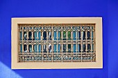 Oriental window in blue exterior wall