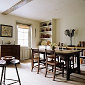 Rustic dining room - wooden dining table and chairs; ceramic bowls on dresser in corner