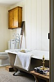 Free-standing vintage bathtub against wood-clad wall; toilet & small, antique, wall-mounted cabinet in corner