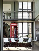 Open-plan interior with dining table, English telephone box as decoration & staircase leading to gallery