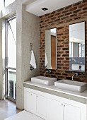 Twin basins on washstand below mirrors on brick wall