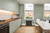 Graue Küchenzeile Ton in Ton mit der Wand in moderner, geräumiger Küche; in der Mitte ein langer Esstisch im Shabby Stil