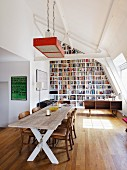 Attic interior with impressive bookcase, rustic dining table and elegant chairs with leather seats