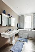 Bathtub with steps below large sash window behind long, twin pedestal washbasin