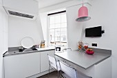 White, modern kitchen with grey console table and pink, bell-shaped pendant lamp