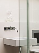 Rectangular, white washbasin with shiny, wall-mounted tap fittings