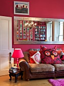 Large wall-mounted mirror with silver frame on hot pink wall above leather couch with large cushion shaped like owl