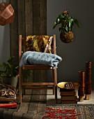 Shopping-Trends für den Winter: Holzstuhl mit Wolldecken, Bodenkissen, Teppiche und Lampe
