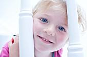 Little girl peeping through banisters
