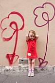 Little girl standing in front of flower motifs spray-painted on wall