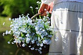 a woman holding a basket with forget-me-nots