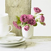 Pink roses in ceramic vase, teacups and side plates