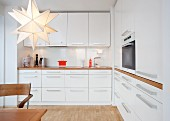 Kitchen with white furnishings, wooden worksurfaces, fitted cooker and star-shaped lamp