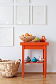 Oranges in wooden bowl and teapots on orange side table