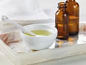 Teebaumöl in einer Schale und in Apothekerflaschen