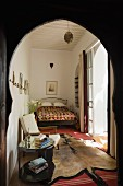 View through Oriental archway into Moroccan bedroom with bed, armchair, side table and animal-skin rug