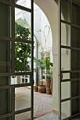 View though open sliding doors into Moroccan courtyard with potted plants on mosaic tiles