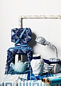 Various, every-day objects wrapped in blue and white fabrics and recognisable by their shapes