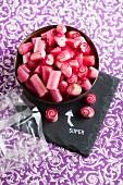 Schale mit roten Zuckerschnecken auf bestempelter Schieferplatte