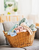 Dirty laundry & bottle of laundry detergent in basket on sofa
