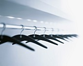 Coat hangers hanging from clothes rack