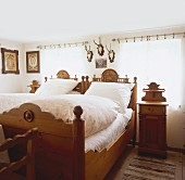 Farmhouse bedroom with ornate carved furniture and hunting trophies