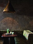 Restaurant table against grey wall with freshly served platter of oysters and cocktails; rustic pendant lamp above table