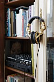 Books and hifi in glass-fronted cabinet; headphones hanging on cabinet key