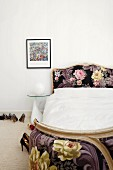 Glass-topped table next to antique, French corbeille bed with new, floral upholstery
