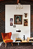Fifties-style, orange armchair next to table lamp on coffee table in front of pictures hung on white panel on brick wall