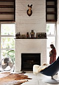 Comfortable shell chair with sheepskin in front of open fireplace in modern country house