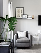 Seating area next to window with simple, grey designer armchair below collection of artworks on wall-mounted shelf