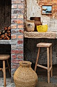 Rattan basket on floor in front of brick wall with masonry shelf and rustic bar stools in Mediterranean ambiance