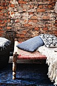 Scatter cushions on antique stool with woven seat in front of rustic brick wall