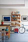 Island kitchen counter on castors and designer, plexiglass stools (Ghost); various artworks, bookshelves and racing bike against wall in background