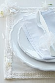 Romantic place setting with fabric place mat decorated with ribbon and lace flowers