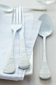 Cutlery with lace trim decorating handles on table