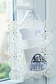 Hand-crafted note rack made from crocheted doilies and lace ribbon hanging on door handle