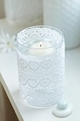 Floating candle in lantern wrapped in lace ribbon