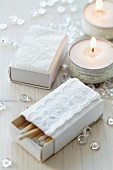 Matchboxes covered in white paper and decorated with lace trim and decorated tealights