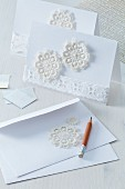 Invitation cards and envelopes decorated with segments of crocheted doily and lace trim