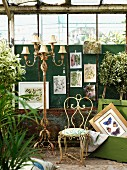 Wrought iron chair and multiple-armed standard lamp in front of pictures of plants hung on wall in rusty greenhouse