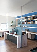 Half-height glass wall with steel supports between living area and office space with shelving on blue-painted wall