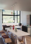 Wooden, workbench-style dining table and stools in open-plan interior; lounge area in panoramic bay window