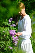 A young woman looking at the flowering lilac