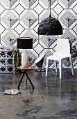 Black and white interior with geometric wallpaper behind white plastic chair and black pendant lamp; table lamp on three-legged side table in foreground