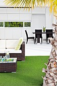 View across terrace area with lounge furniture, artificial turf and palm-tree trunk to dining area with white fitted kitchen and ribbon window with view of garden