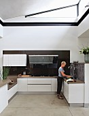 Open-plan, white, designer fitted kitchen with triangular transom light below ceiling; woman at kitchen counter