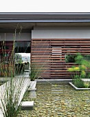 Boardwalk next to pool in garden of contemporary house with slatted wooden cladding on facade